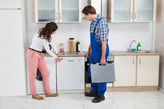 Woman Showing Dishwasher To Worker Stock Photos