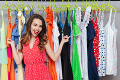 Woman showing at dresses. Cheerful young woman showing at hanger with dresses royalty free stock photo