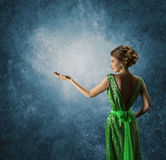 Woman Showing Empty Hand, Elegant Model Rich Gown Display. Woman in Green Dress Showing Empty Hand, Elegant Model in Rich Gown Display Jewelry over Gray stock photography