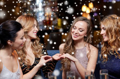 Woman showing engagement ring to her friends. Christmas, friends, bachelorette party and winter holidays concept - happy women showing engagement ring to her Royalty Free Stock Image