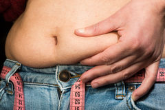 Woman showing fat belly. Pink tape measure Royalty Free Stock Image