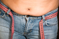 Woman showing fat belly. Pink tape measure Stock Images