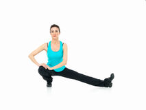 Woman showing fitness routine, white background. Sexy, young woman showing fitness moves, on white background Royalty Free Stock Photography