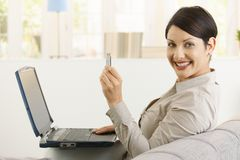 Woman showing flash drive. Young woman using laptop computer, showing up flash drive, smiling Stock Photography