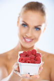 Woman showing fresh and nutritious raspberries. Cheerful young woman showing a plastic container full of fresh and nutritious raspberries  natural source of Royalty Free Stock Photo
