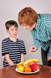 Woman showing fruit to a young boy Stock Images