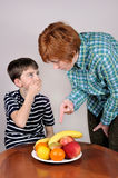 Woman showing fruit to a young boy. Strict women showing a cute young boy fruit he has to eat Stock Photography