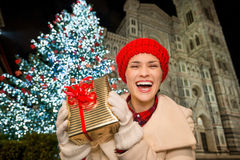 Woman showing gift box near Christmas tree in Florence, Italy. Smiling young woman in white coat showing gift box in front of Christmas tree near Duomo in the royalty free stock images
