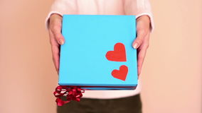 Woman showing a gift. Hands of a woman showing a gift: blue box with two red hearts and a ribbon stock video footage