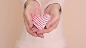 Woman showing a gift. Hands of a woman showing a gift: little heart with red and white stripes stock video footage