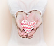 Woman showing a gift. Hands of a woman showing a gift: little heart with red and white stripes. Selective focus Stock Photos