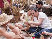 Woman showing girl how to weave a wreath of ears Stock Images