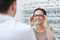 Woman showing glasses to optician at optics store Royalty Free Stock Photos