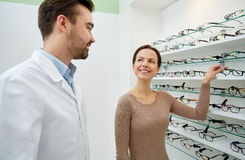 Woman showing glasses to optician at optics store Royalty Free Stock Photography