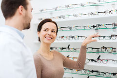Woman showing glasses to optician at optics store Stock Photography