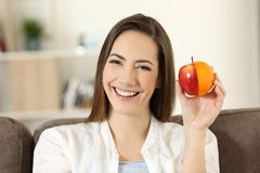 Woman showing an half orange and apple. Sitting on a couch in the living room at home royalty free stock images