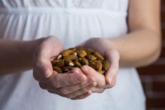 Woman showing handful of almonds Stock Photo