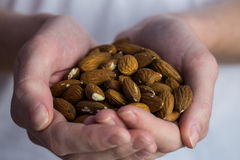 Woman showing handful of almonds Royalty Free Stock Image