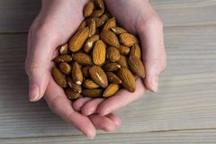 Woman showing handful of almonds Stock Photos