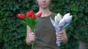 Woman showing handmade textile bunch of flowers to camera, reuse of cloth