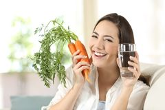 Woman showing healthy carrots and water glass Royalty Free Stock Photos