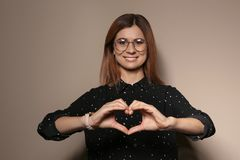 Woman showing HEART gesture in sign language. On color background stock photos