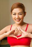 Woman showing heart hand symbol Stock Photos