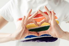 Woman showing heart with hands. Cropped image of woman standing in a white shirt with rainbow and showing heart with hands isolated on white royalty free stock photos
