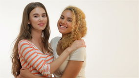 Woman showing heart shape gesture. Brown-haired caucasian and red-haired mulatto girls  standing in an embrace, showing heart shape gesture and smiling at the stock video