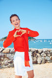 Woman showing heart shaped hands in front of lagoon with yachts Royalty Free Stock Images