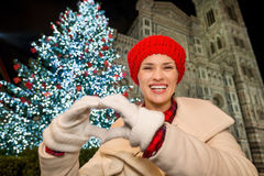 Woman showing heart shaped hands near Christmas tree in Florence. Happy young woman showing heart shaped hands in front of Christmas tree near Duomo in the royalty free stock photography