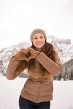 Woman showing heart shaped hands among snow-capped mountains Stock Photo