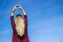 Woman showing heart towards sky stock photos