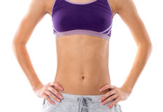 Woman showing her abdominals. Young woman in purple sports top and grey shorts showing her abdominals on white background in studio Royalty Free Stock Photo