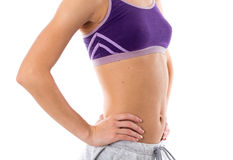 Woman showing her abdominals. Young sportive woman in purple sports top and grey shorts showing her abdominals on white background in studio Stock Photos