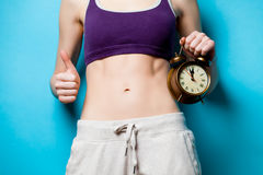 Woman showing her abs with alarm clock Royalty Free Stock Image