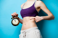 Woman showing her abs with alarm clock Stock Photography