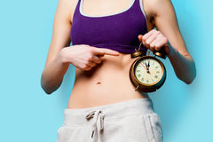 Woman showing her abs with alarm clock Stock Image