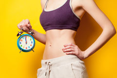 Woman showing her abs with alarm clock Royalty Free Stock Photos