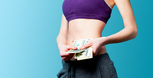 Woman showing her abs with dollars after weight loss Royalty Free Stock Image