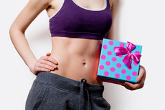 Woman showing her abs with gift box Stock Image