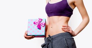 Woman showing her abs with gift box Stock Images