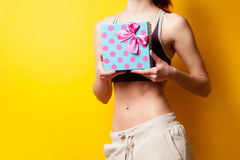 Woman showing her abs with gift box Royalty Free Stock Images