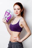 Woman showing her abs with gumshoes Royalty Free Stock Images