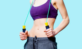 Woman showing her abs with jumping-rope Stock Image