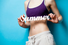 Woman showing her abs with Summer word inscription Stock Images