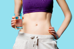 Woman showing her abs with water glass Stock Photo