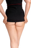 Woman showing her buttock. A young woman standing from the back in a black dress, lifting her dress and showing her bottom stock images