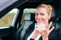 Woman showing her driving license out of car Stock Photos