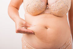 Woman showing her fat stomach. Woman showing her fat belly Royalty Free Stock Photography